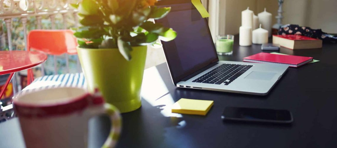 Freelancer needs workstation, workplace with open laptop computer, smartphone, notebook, cup or mug and pot of flowers,online learning or distance work concept, modern table at window in home interior